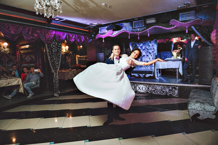 romantic couple dancing on their wedding. Dance of the bride and groom. In the restaurant with purple, lilac, mauve design. Happy and love dancing.