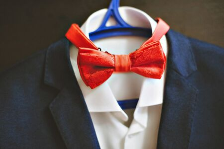 midriff: Photo of a blue suit with white shirt and red tie.
