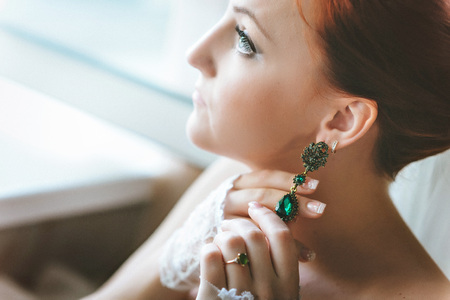 green gemstone: Earrings with green gemstone. Beautiful jewelry. Aged gold