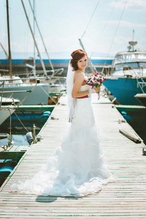 dowry: Bride in white wedding dress with a train, stands on the pier in the port Stock Photo
