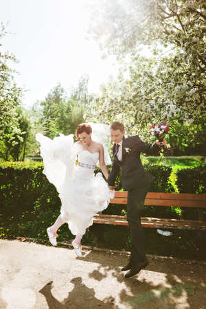 pompous: Wedding couple having fun and jumping together.