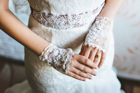 Wedding gloves on hands of bride, close-up. with a gold ring and green gem