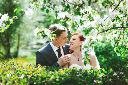 pakistani ethnicity: Portrait of young happy loving couple in green on a background of white flowers. Beautiful Sunny spring weather