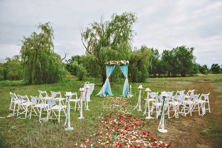 set up: wedding decor on the lawn, wedding arch, chairs with ribbons. turquoise, purple and white. The rose petals on the ground. Wedding ceremony