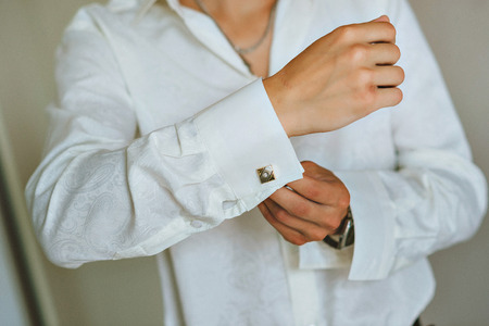 hand cuff: close up of a hand man how wears white shirt and cufflink