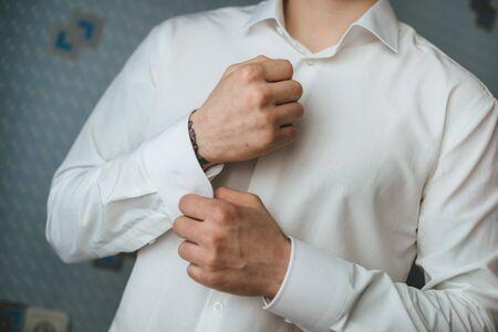cufflink: close up of a hand man how wears white shirt and cufflink
