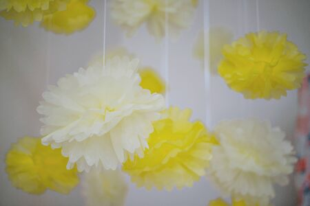 Yellow POM-poms out of paper. The decor for the occasion. Background.