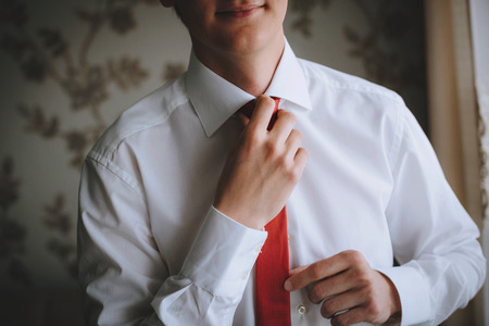 red tie: The man ties a red tie, in white shirt.