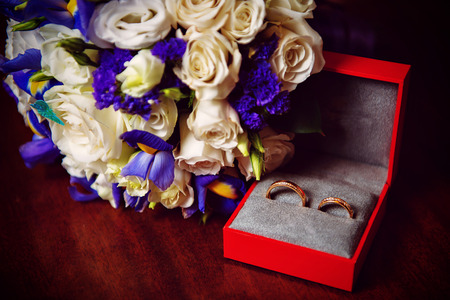 Two wedding rings with white flower in the background in the red box