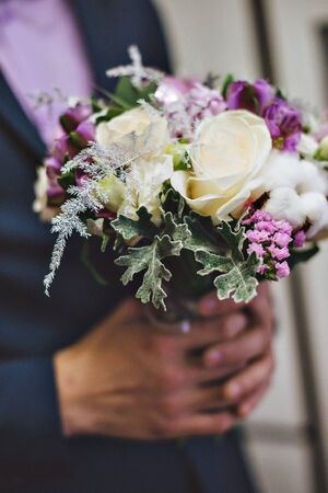 Lilac wedding bouquet in hands of the groom Stock Photo