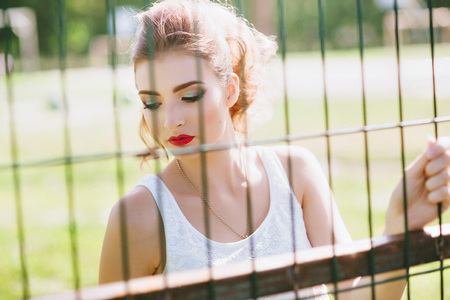 Beautiful young woman on a green football field. Closeup portrait of. Red lips