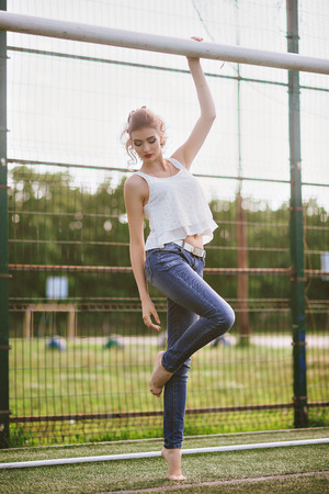 Beautiful young woman on a green football field. Girl standing at football gate, dressed in blue jeans, a white t-shirt. Red lips Stock Photo