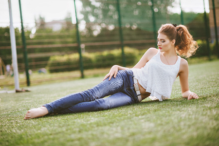 Young woman sitting on a green football field, dressed in blue jeans, a white t-shirt. Red lips