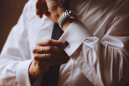 The man wears cufflinks on a white shirt. Mens watch Stock Photo