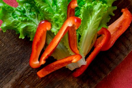 cornsalad: Salad of fresh vegetables. Red pepper and green salad on dark wooden background. Vegetarian food