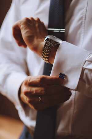 french cuffs: The man wears cufflinks on a white shirt. Mens watch Stock Photo