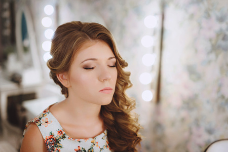 Stylist makes makeup and hair young woman, the bride. Applying lipstick. Brings eyes. Brides morning Stock Photo