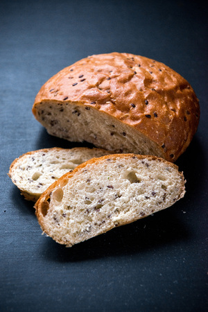 The whole grain bread with flax seeds, on the blackboard Stock Photo