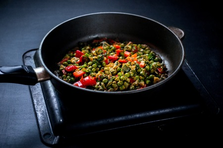 Vegetable stew with green peas, red pepper, onion and zucchini, and spices. In a frying pan on a black background