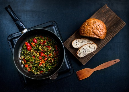 Vegetable stew with green peas, red pepper, onion and zucchini and spices. In a frying pan on a black background. On a wooden platform grain bread with flax seeds