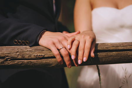 Groom and brides hands with rings, closeup view