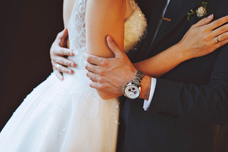 Hands of the bride and groom. A man hugs a woman. Watch Stock Photo