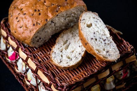 Grain loaf with flax seeds, a wicker basket for the bread Stock Photo