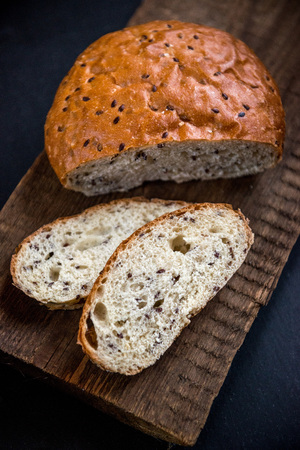 Grain loaf with flax seeds, on slate and wooden background