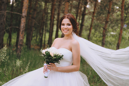 Wedding day. The bride in a pine forest, holding a bouquet of white roses, she developed veil
