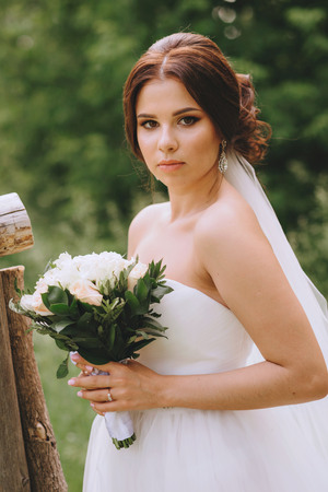 Wedding day. The bride in a pine forest, holding a bouquet of white roses. Closeup portrait of. Stock Photo