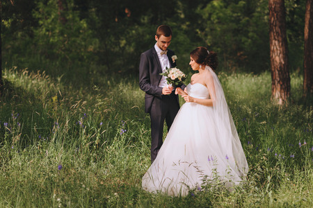 Wedding couple in a Park. The groom approaches the bride gives her wedding bouquet