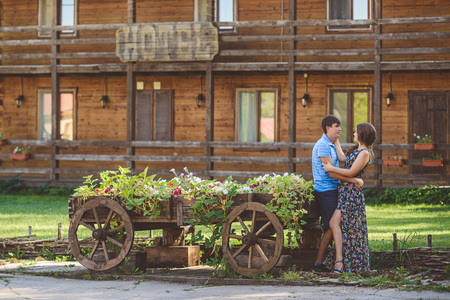 Romantic young couple hugging each other near a decorative wooden carts with flowers, on a background of rustic style