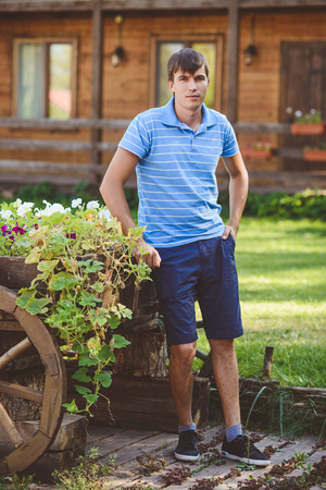 A young man in a blue shirt and blue shorts near decorative wooden carts with flowers, on a background of rustic style. Smiling looking at the camera