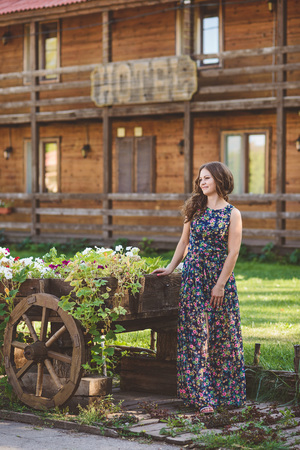 Young woman with beautiful long hair in floral dress near decorative wooden carts with flowers, on a background of rustic style. Smiling, looking to the side Stock Photo
