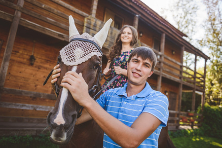 Romantic young couple in love, a walk on a horse on nature background and wooden country-style hotel. Young woman sitting on horseback. The man stroked the horses head. Concept: love, romance, Hobbies.