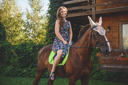 Young woman sitting on horseback, walk in the nature Stock Photo