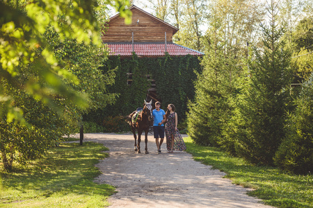 Romantic young couple in love, a walk on a horse on nature background and wooden country-style hotel. A man and a young woman out for a walk. Concept: love, romance, Hobbies. Stock Photo