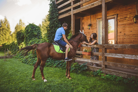 Romantic young couple in love, a walk on a horse on nature background and wooden country-style hotel. A man sits astride a horse, goes to a young W. Concept: love, romance, Hobbies.