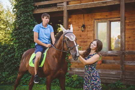 Romantic young couple in love, a walk on a horse on nature background and wooden country-style hotel. A man sits astride a horse.e. Concept: love, romance, Hobbies.