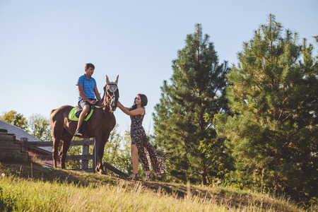 Romantic young couple in love, walk on horseback, on nature background. A woman touches the hand of a horse. Concept: love, romance, Hobbies.