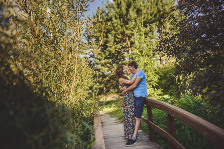 Happy romantic couple in the village, stroll on the wooden bridge. Young beautiful woman and man hugging each other