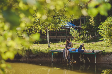 Happy romantic couple in the village, stroll on the wooden bridge near the lake. The man on the lap of a young woman Stock Photo