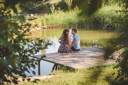 Happy romantic couple on a wooden bridge near the lake. Man and a young woman talking sitting on the shore of the lake