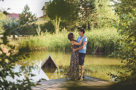 Happy romantic couple in the village, stroll on the wooden bridge near the lake. Young beautiful woman and man hugging each other