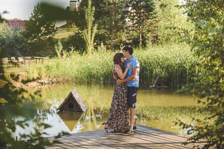 Happy romantic couple on a wooden bridge near the lake. Man embraces a young woman
