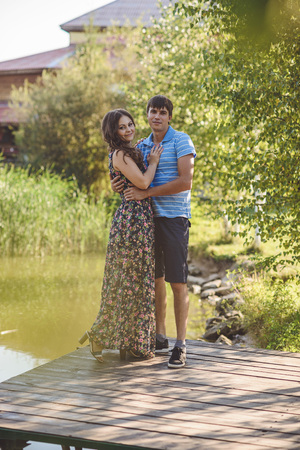 Happy romantic couple on a wooden bridge near the lake. Man and young woman looking at the camera Stock Photo