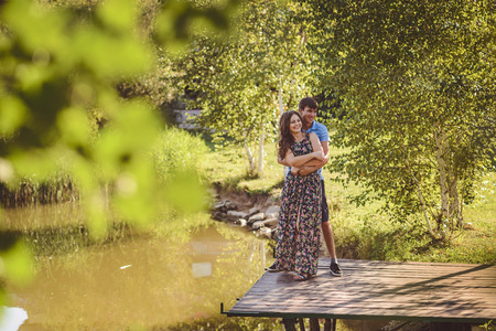 Happy romantic couple on a wooden bridge near the lake. Man embraces a young woman, they have fun laughing