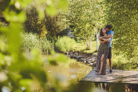 Happy romantic couple on a wooden bridge near the lake. Man embraces and kisses a young woman