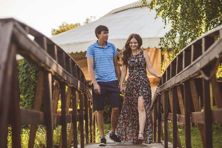 Happy romantic couple in the village, stroll on the wooden bridge Stock Photo