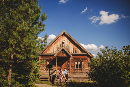 Couple men and women in the village, near a wooden house Stock Photo